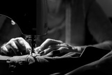 Close Up On Sewing Machine And Seamstress' Hand While She Is Working. Black And White