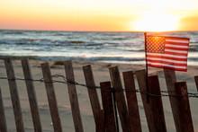 Sunset Illuminating American Flag On Beach Fence With Lake Michigan Background