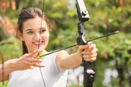 Young woman practicing archery outdoors Canvas Print