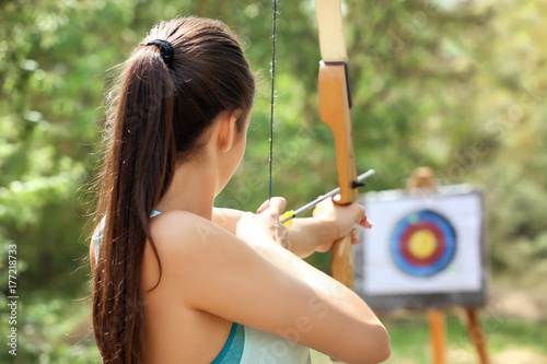 Valokuva Young woman practicing archery outdoors