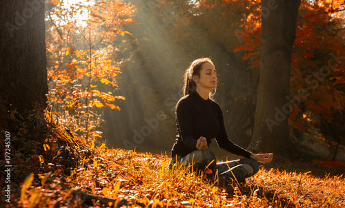 Staande foto School de yoga A young woman make yoga position at sunrise. in the autumn forest.