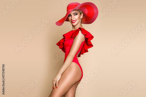 Obraz Portrait of an elegant woman in a hat, red bikini and red lips on a beige background - fototapety do salonu
