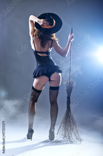 Fototapeta Background to Halloween, sexy woman in a witch costume with a broom, view from the back