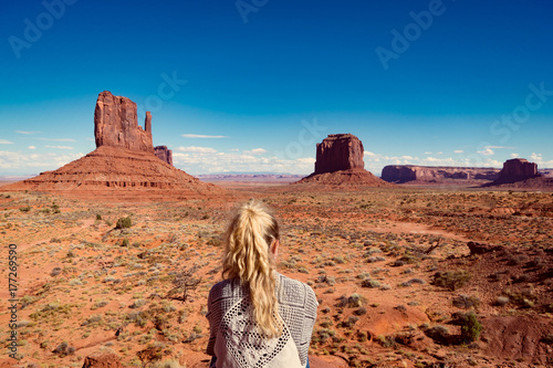 Photo  woman sitting in Monument Valley with red rocks overview