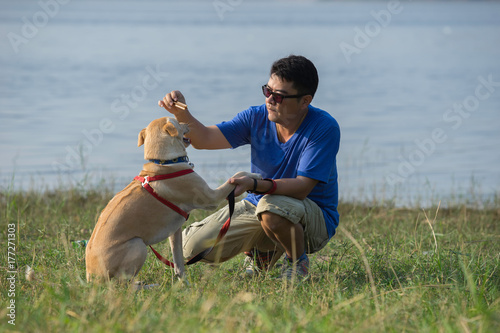 A man is playing with a lovely dog beside the reservoir. Fototapet