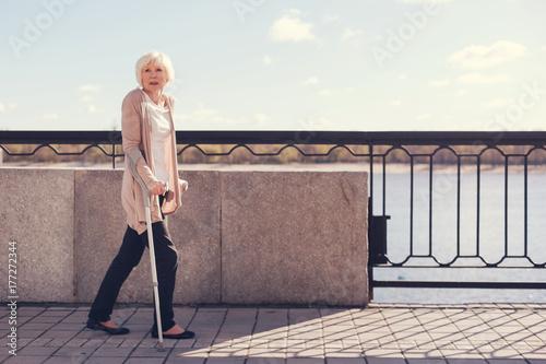 Fototapeta Elderly woman walking along the bridge on crutches