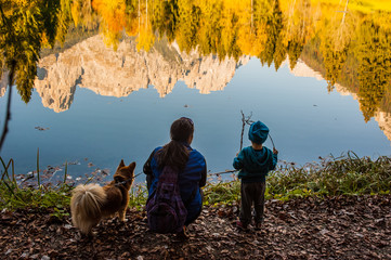 a baby with her mother and dog on the shore of the lake on which the mountains are reflected