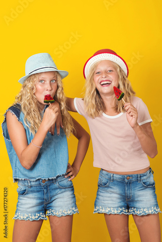 Photo  Girls twins holding lollipop and have fun together on yellow background