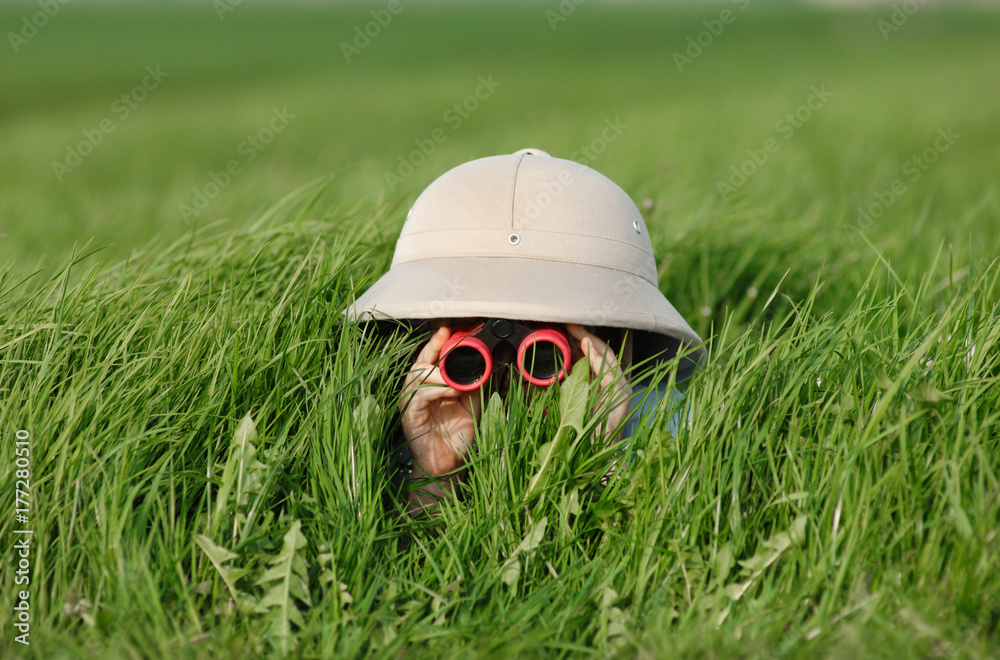 Fototapety, obrazy: Little Boy with Binoculars and safari Hat, laying in the grass searching for Knowledge