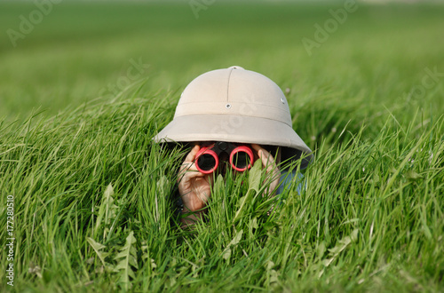 Fotografie, Obraz Little Boy with Binoculars and safari Hat, laying in the grass searching for Kno