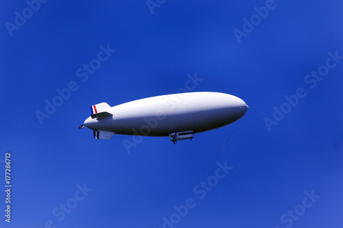 Photo A zeppelin flying in the blue sky
