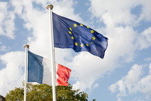 Two Flags With French And European In Wind And Cloud