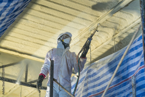 Obraz Technician spraying foam insulation using Plural Component Gun for polyurethane foam - Repair tool in the white protect suit applies a construction foam from the gun to the roof of a warehouse. - fototapety do salonu