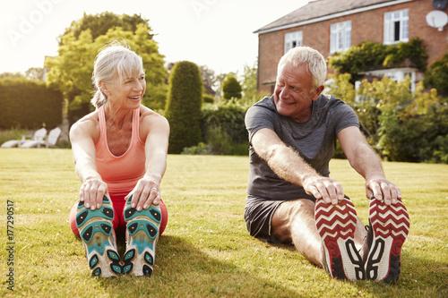 Plakat Zdrowa Starsza para ćwiczy w ogródzie Wpólnie