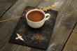 A cup of hot chocolate with cocoa powder on wooden background