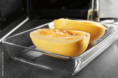 Cut spaghetti squash in baking dish on table