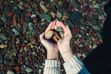 Hands Holding Colorful Rocks O...