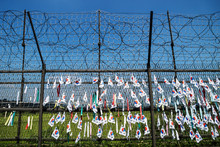 Fence With Barbed Wire And South Korean Flags At The Demilitarised Zone DMZ At The Freedom Bridge With Blue Sky, South Korea, Asia