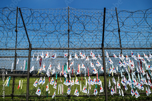 Fotografie, Obraz  Fence with barbed wire and south korean flags at the demilitarised zone DMZ at t