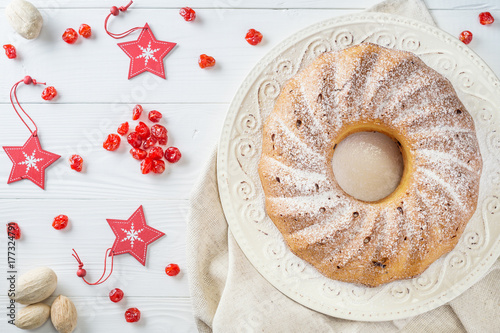 Fotomural Traditional Christmas bundt cake with raisins, dried cherries, cranberry and sugar powder on a white plate