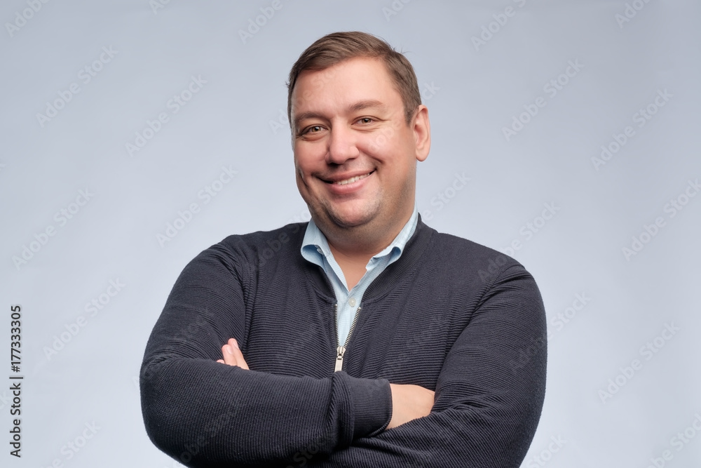 Fototapeta Half body portrait of confident middle aged man with folded arms looking at camera