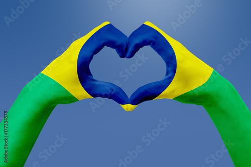 Plakat Flaga rąk Brazylii, kształt serca. Pojęcie kraju symbol, na niebieskim niebie.