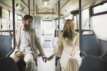 Young Couple Sitting In An Empty Bus And Holding Hands