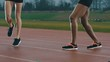 Low angle view female athletes warming up at running track in the rain