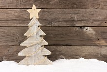 Shabby Chic Wooden Christmas Tree With Twine Garland Standing In Snow Against A Rustic Wood Background
