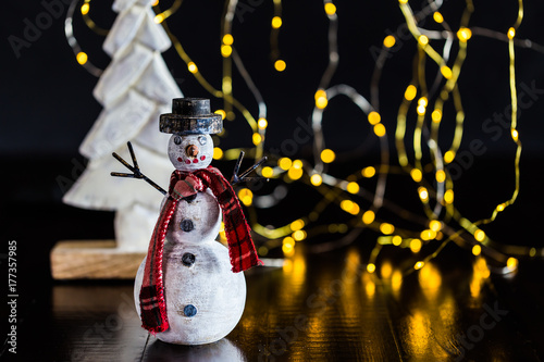 hand made wooden snowman tree and blurry christmas light on the rustic wood table
