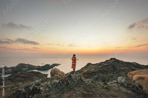 Back view of young woman looking the sunrise from a cliff from far away.