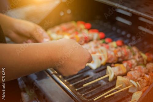 Plakat Azjatyccy ludzie gotują dla grupy rodzin jeść grill (grill) dla rodziny cieszącej się świętami Bożego Narodzenia i Nowego Roku.