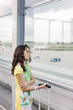 Vertical photo of a girl who is watching the planes at the airport while waiting
