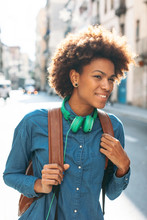 Afro American Woman With Leather Backpack And Green Headphones Smiling In Outdoors.