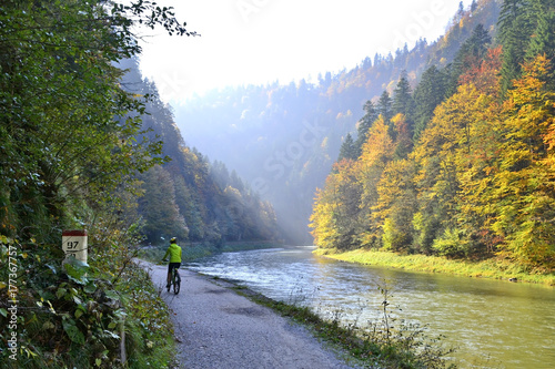 The woman is riding a bicycle along Dunajec river, Pieniny mountains