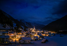 Nighttime View Of Cozy Austrian Village In The Mountains In Winter