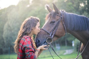 Beautiful girl kissing her horse
