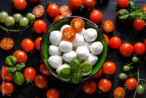 Plakat Włoskie jedzenie. Mozzarella, pomidory i bazylia na ciemnym łupku, nad głową
