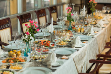 Beautiful Festive Table Served For Wedding Celebration Dinner At Home Or Restaurant Interior. Plenty Of Different Food And Cutlery. Long Table Covered With Tablecloth And Decorated With Flowers.