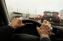 Mature Mans Hands Clasping The Steering Wheel In His Car During A Rush Hour Traffic Jam