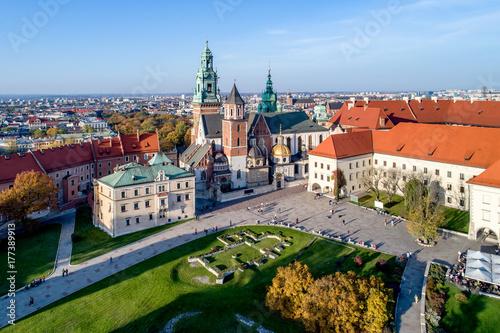 Fototapeta Królewska Katedra gotycka na Wawelu w Krakowie, z renesansową kaplicą Zygmuntowską ze złotą kopułą, częścią Zamku na Wawelu, podwórzem, parkiem i turystami. Widok z lotu ptaka o zachodzie słońca w upadku