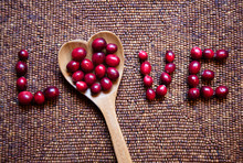 Fresh Cranberries And A Heart Shaped Spoon Spelling The Word LOVE