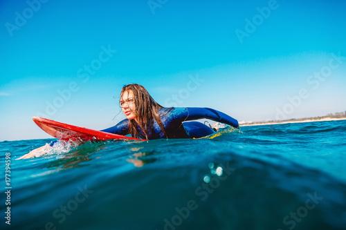 Plakat Surfer dziewczyna na deskę surfingową. Kobieta w oceanie podczas surfowania.