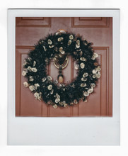 A Halloween Wreath With Doll Head Tied In The Knocker.