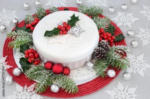 Zdjęcie XXL Lukrowane ciasto Boże Narodzenie z holly, jodła, czerwone bombki i dekoracje białe płatki śniegu z srebrną folią owinięte czekoladki na tle świecidełka.