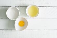 Baking Ingredients- Sugar, Egg White, Egg Yolk On Wooden Board.