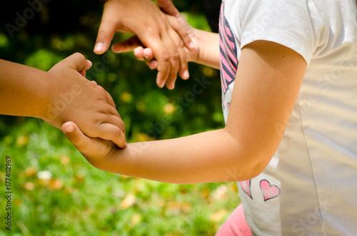 Plakat młoda dziewczyna łączy ręce z matką, aby grać w jasny, słoneczny dzień