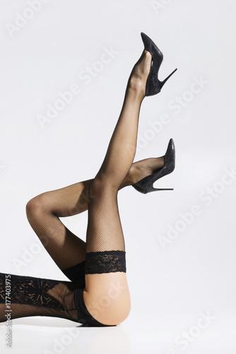 Plakat Piękne i seksowne kobiece nogi. Dopasowanie i uwodzicielska kobieta w nylonowych pończochach.