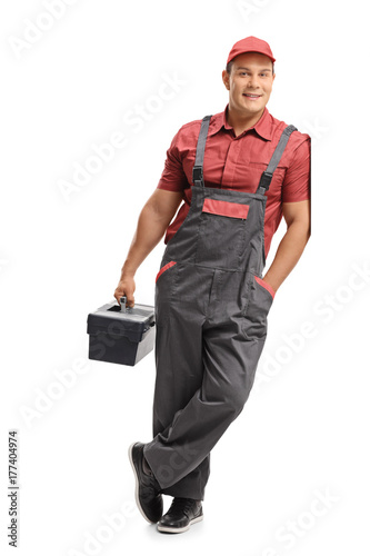Fotografía  Repairman holding a toolbox and leaning against a wall