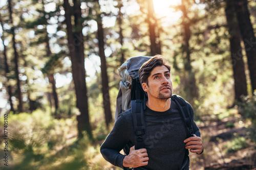 Fényképezés  Man walking in forest wearing a backpack